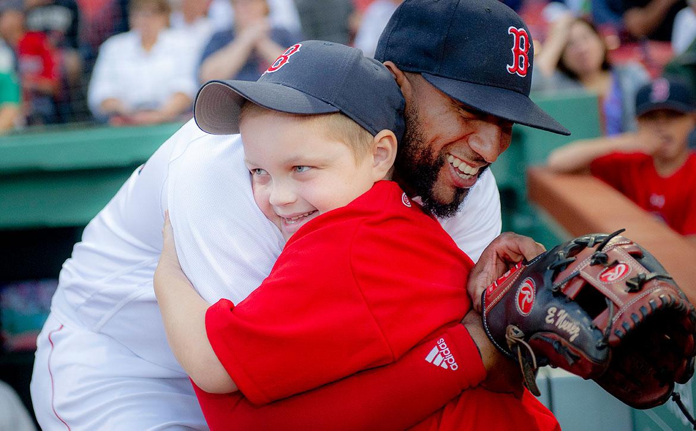 Red Sox player Eduardo Núñez hugs a young Dana-Farber patient