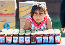 Smiling girl with jam jars