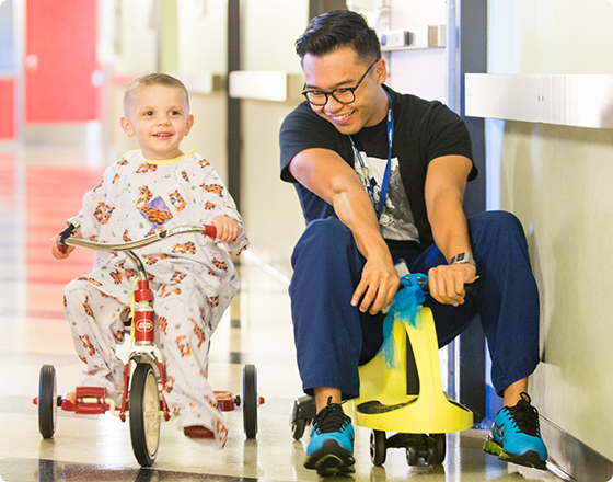 Caregiver and child riding tricycles together.