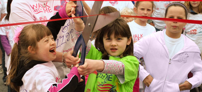 Two kids cutting a ribbon at Walk With Me