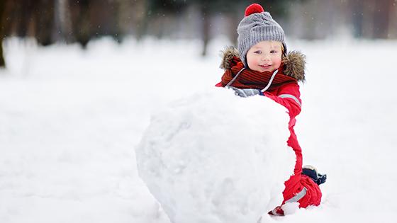 Little boy rolling a snowball