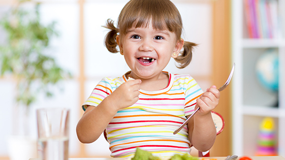 Little girl eating salad