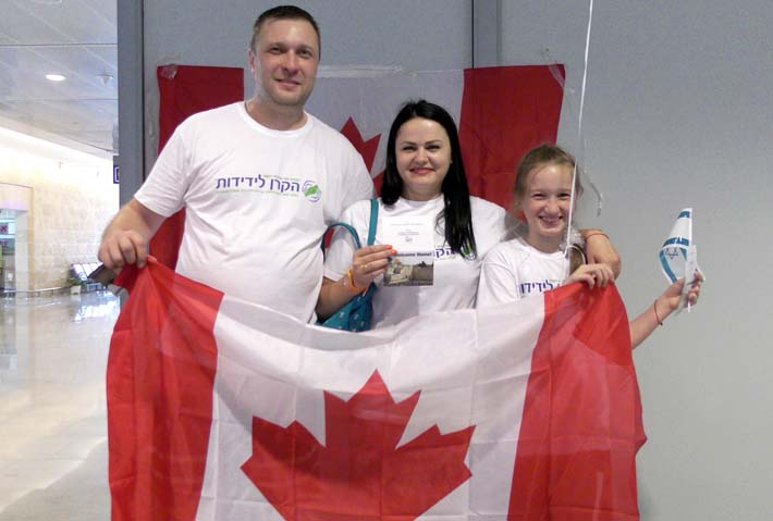 family holding Canadian flag