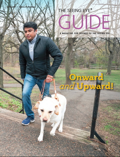 The cover of The Guide Fall 2020 shows Seeing Eye graduate Mahesh Mathew with a yellow Labrador/golden retriever cross walking up stairs in a park.